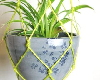 Hanging grey planter with bright green macramé
