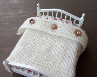 White blanket with wooden buttons dollhouse bed