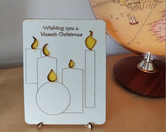 Christmas candle design card, wooden laser-cut, yellow flame cut outs and 'Wishing you a blessed Christmas'  engraved.