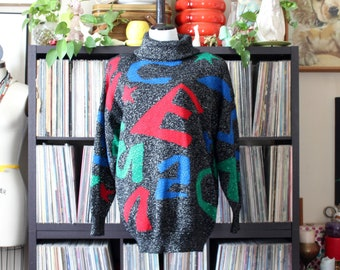 vintage oversized sweater with colorful alphabet letter jumble, chunky turtleneck, shoulder pads, metallic black, approx womens medium