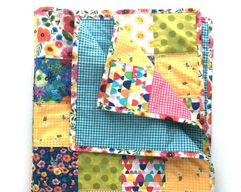 Kitty Garden Handmade Baby Quilt: Colorful small quilt made from a patchwork of cotton fabrics.