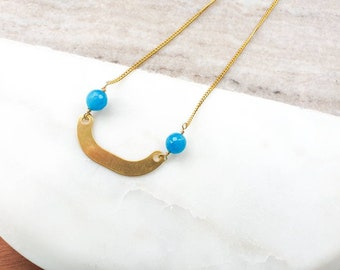Geometric necklace with blue  jade beads and brass curved accent.