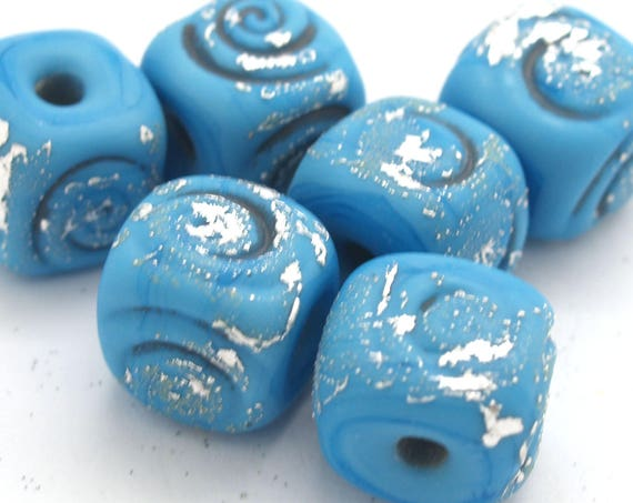 Dark turquoise cube beads with spiral texture.