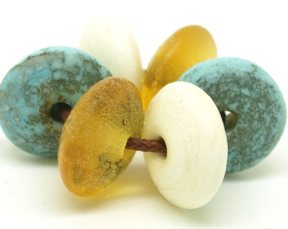 Aged disc bead pairs in aqua, ivory and amber.
