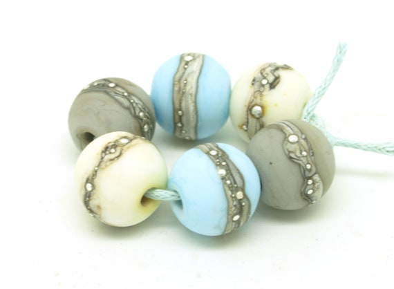 Round bead pairs in pastel shades with silvered ivory and wire.