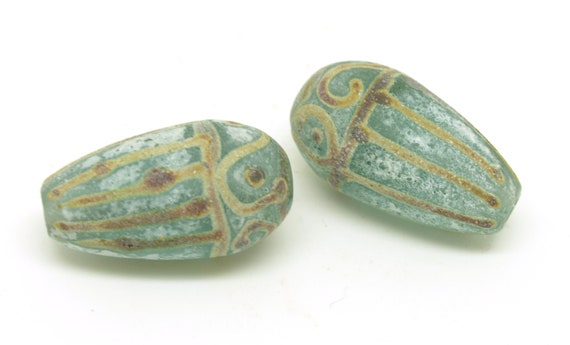 Aged green teardrop beads with raku design.