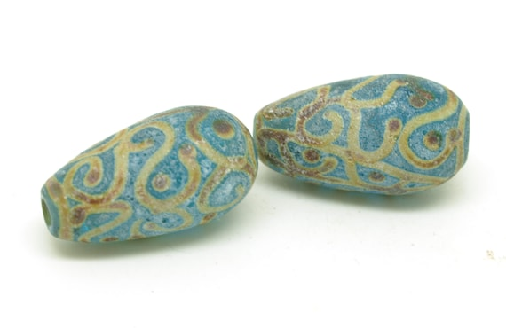 Aged aqua beads with raku scroll design.
