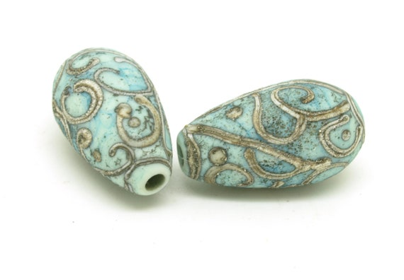 Aged copper green drops with silvered ivory scroll design.