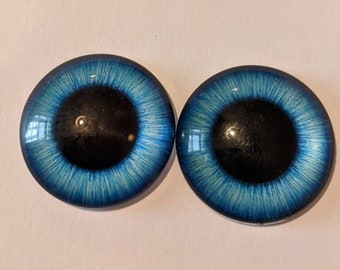 One pair of glass eyes blue colour various colours and sizes
