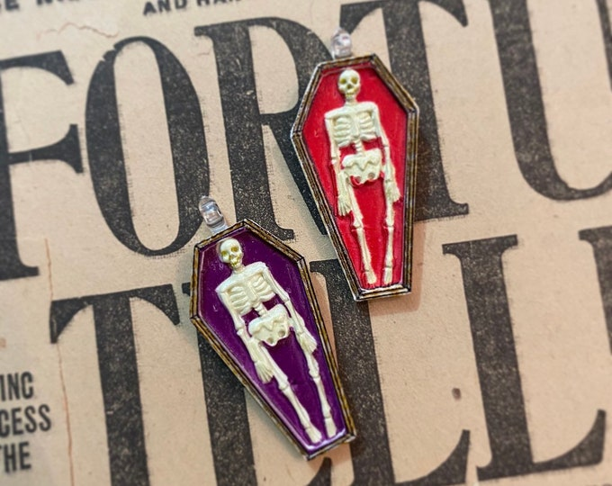 1pc SKELETON CASKET PENDANT Miniature Resin Resting Bones Toe Pincher Coffin Jewelry Halloween Fun Red + Purple Your Choice