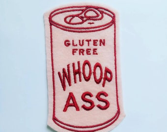 Iron on Patch Can of Gluten Free Whoop Ass Applique in pink felt with burgundy embroidery thread