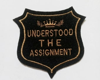 Understood The Assignment in gold embroidery thread and black felt badge iron on patch,  embroidered patch, patches for jackets