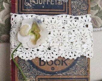 Assemblage on vintage book cover, vintage lace, antique millinery flower