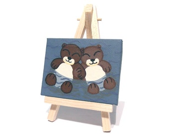 Sleeping Otters Miniature Art - small acrylic painting of 2 cute otters holding paws. Water animal mini canvas on easel by Kim Onyskiw
