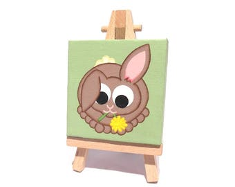 Cute Rabbit Miniature Art - a small original painting of a cartoon brown bunny munching on a yellow flower. Mini canvas with easel or ribbon