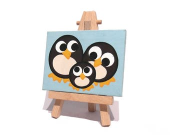 Penguin Family Miniature Art - original acrylic painting of cute cartoon penguins on a turquoise background. Mini canvas with easel