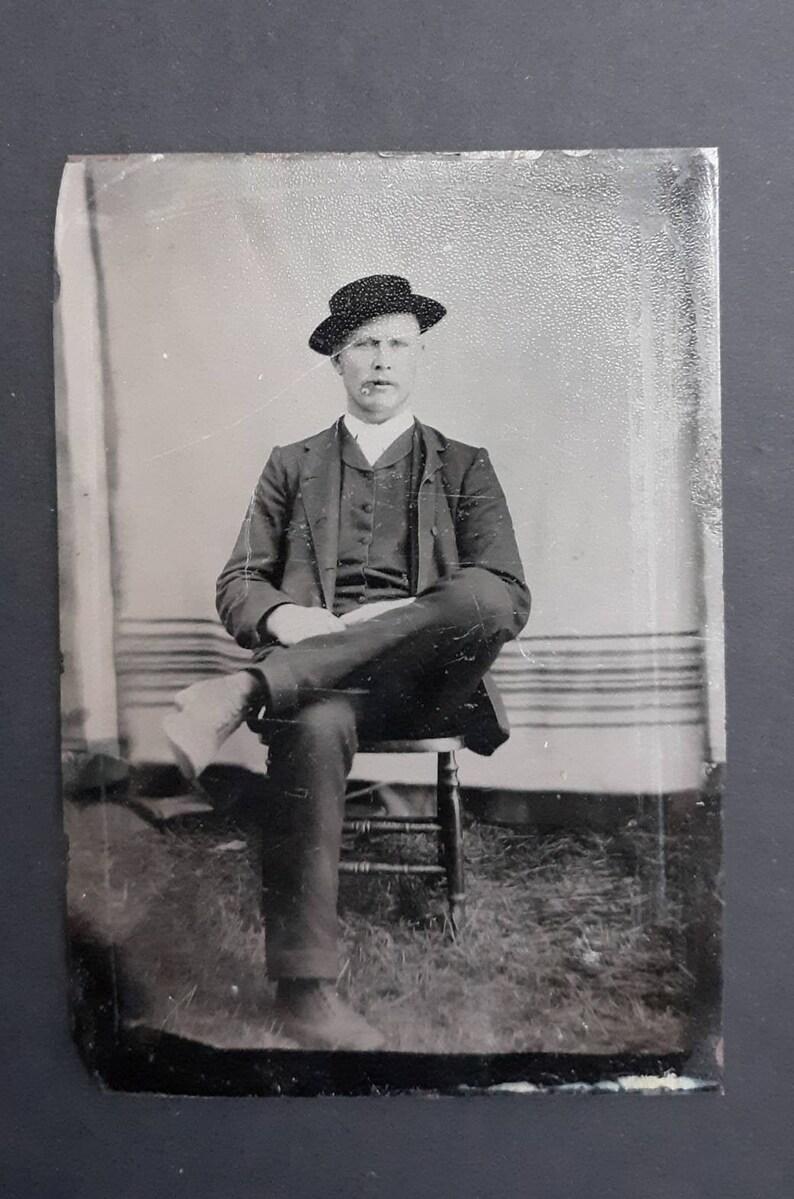Attractive man wearing hat smoking cigar outdoor tintype image 0