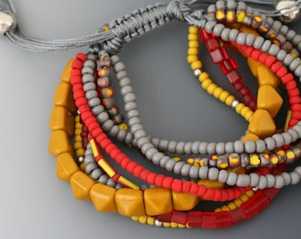 Multi-strand bracelet with macrame sliding knot. One size fits most. Yellow, red, and gray jewelry.