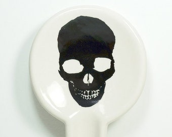 A Spoon Rest glazed in Clear Natural with a pitch Black Skull silhouette on it. Pick Your Color/Pick Your Print