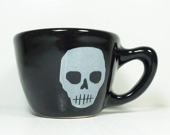 Halloween ready 12oz cup/mug w/ a Voodoo Skull White print on our Blackest Black gloss glaze