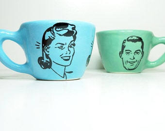 a pair of 12oz cups with a guy + a gal, seen here on cloudless & blue-green glazes - Made to Order / Pick Your Colour