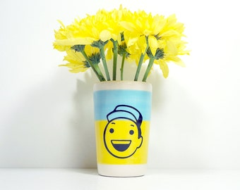 itty bitty cylinder in colour block of sky blue & yellow, with a hey! dude on it, made to order.