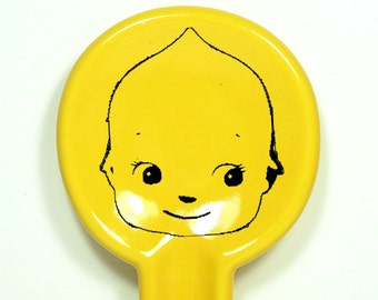 A Spoon Rest with a Kewpie Cabeza/Head print shown here on Lemon Butter Yellow glaze. Pick Your Color/Pick Your Print