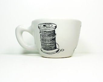 12oz cup with a spool of thread + needle prints, shown here on white glaze - Made to Order / Pick Your Colour