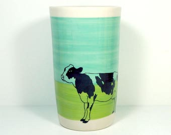 a tall porcelain cylinder/vase/utensil holder with a Holstein Cow print on a colorblock of Blue Green and Leaf, In Stock / Ready to Ship.