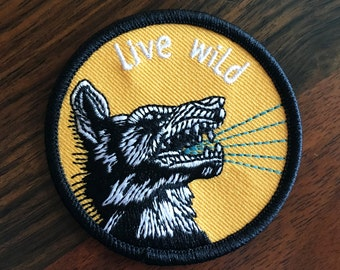 Live Wild - round embroidered iron-on patch featuring roaring wolf