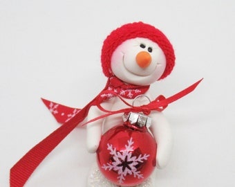 Can I help with the tree. Snowman ornament with a red snowflake ornament, polymer clay snowman
