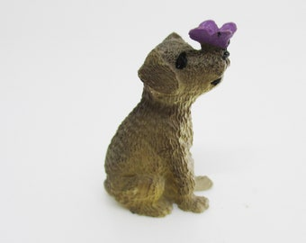miniature sitting dog figurine and purple butterfly