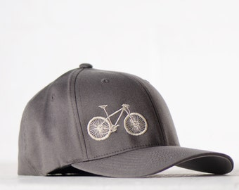 9c34dcc08911 S M MOUNTAIN BIKE flexfit fitted hat, cream embroidery bicycle on charcoal  cap