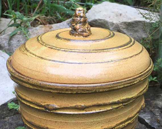 ceramic lidded vessel in golden beige and black