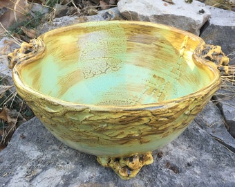large handled ceramic serving bowl in pale green, beige, and golden yellow