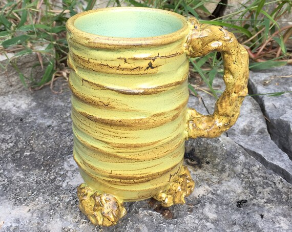 medium sized ceramic mug in beige, golden yellow, and pale green