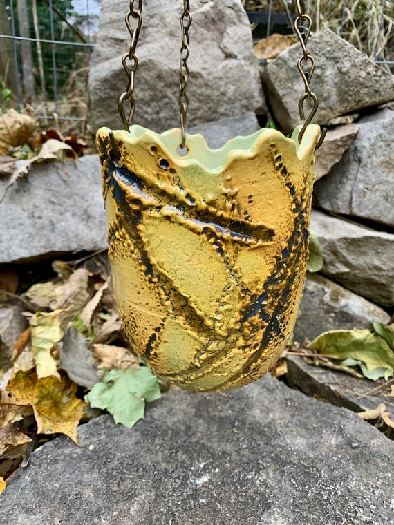 ceramic hanging pot in golden yellow, black, and melon green
