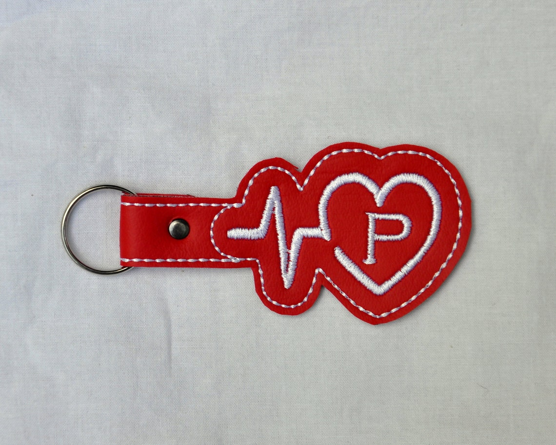 embroidered red vinyl with a heart and a heartbeat with an initial