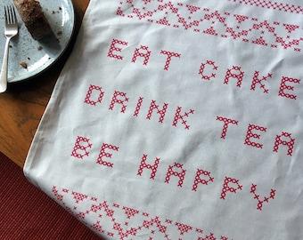 Eat Cake, Drink Tea, Be Happy screenprinted cross-stitch tea towel
