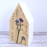 Real pressed flower on little wooden house. Modern botanical decor.