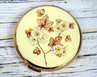 Vintage Stratton mirror compact; enamel lid with yellow, brown and white floral pattern.