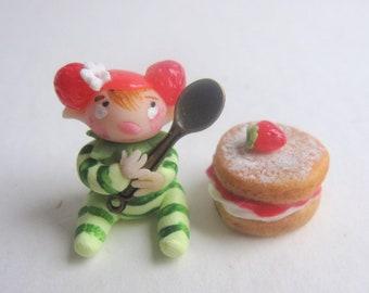 Tiny strawberry pixie figurine with faux victoria sponge cake