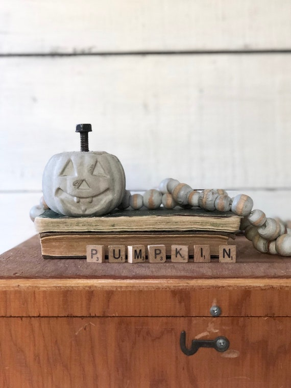 Small Concrete Pumpkin Halloween jack-o-lantern with rusty bolt stem