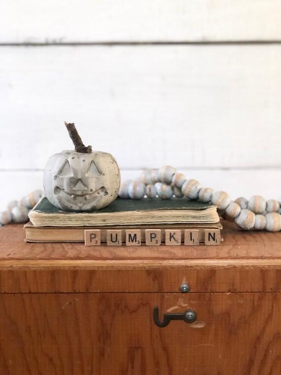 Small Concrete Pumpkin Halloween jack-o-lantern with twig stem