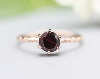 Round faceted garnet ring in prongs setting with 18k rose gold texture design band