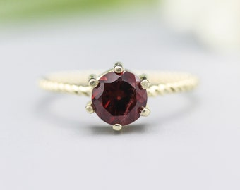 Round faceted garnet ring in prongs setting with 14k gold twist band