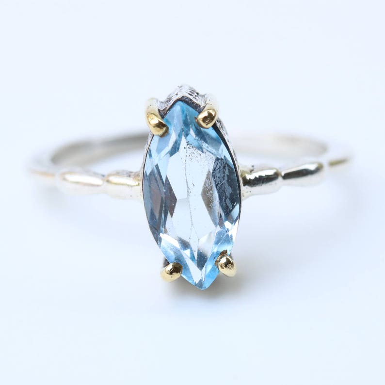 Marquis faceted Swiss blue topaz ring in silver bezel and brass prongs setting on sterling silver band