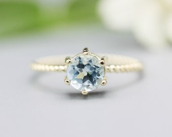Round faceted  blue topaz ring in prongs setting with 14k gold twist band