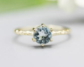 Round faceted blue topaz ring in prongs setting with 14k gold texture design band