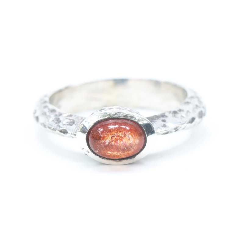 Oval cabochon Sunstone ring in silver bezel setting with sterling silver oxidized texture thick band